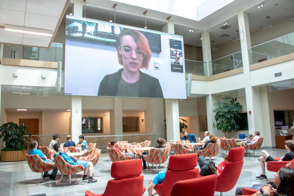 Mary Kenney appears on the Franklin Hall commons screen. Students watch from the commons chairs.