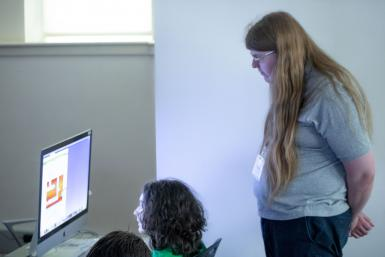 Counselor Avery Cortell watches a student create an illustration on a computer.
