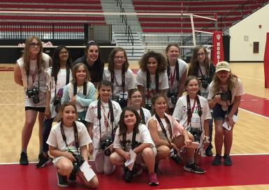 Fourteen girl scouts pose with volleyball player Kamryn Malloy on the court.