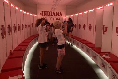Girls take photos in the IU volleyball locker room.