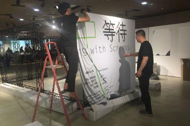 Shaw Xu Zhifeng and professor Zhou Hongtao set up the exhibition frame.