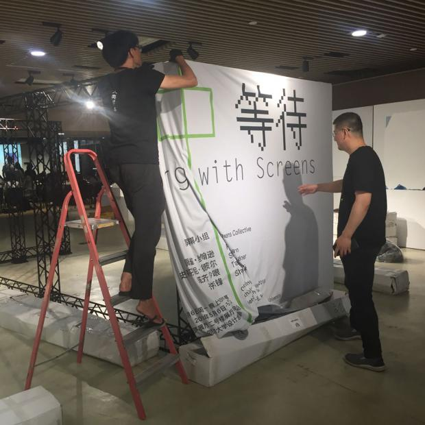 Shaw Xu Zhifeng and professor Zhou Hongtao set up the exhibition frame.