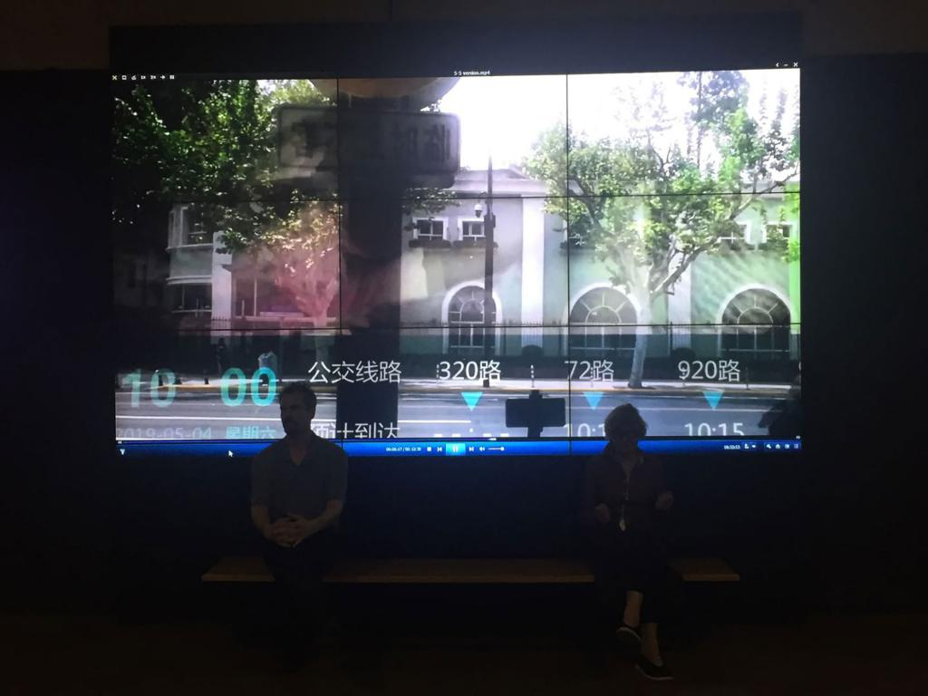 Artist Petra Johnson and Marceau Chenault sit in front of a video screen depicting an empty streetscape.