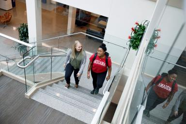 Two women walk up the stairs in the commons