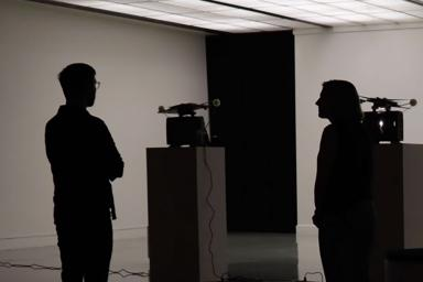 Two people in a darkened room standing in front of two film projectors on pedestals.