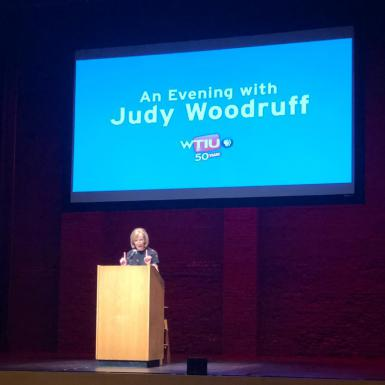 "Judy Woodruff speaks at a podium below a sign that says ""An Evening with Judy Woodruff."""