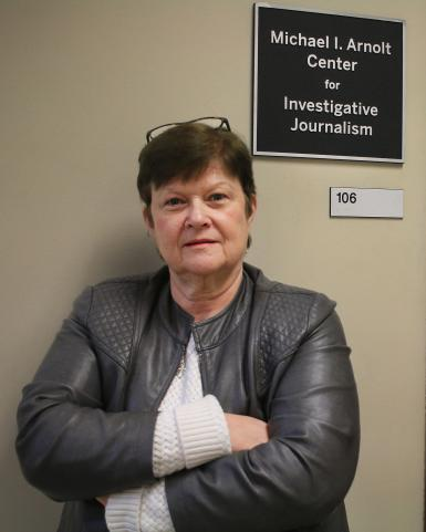 "Kathleen Johnston standing in front a sign that says ""Michael I. Arnolt Center for Investigative Journalism"""