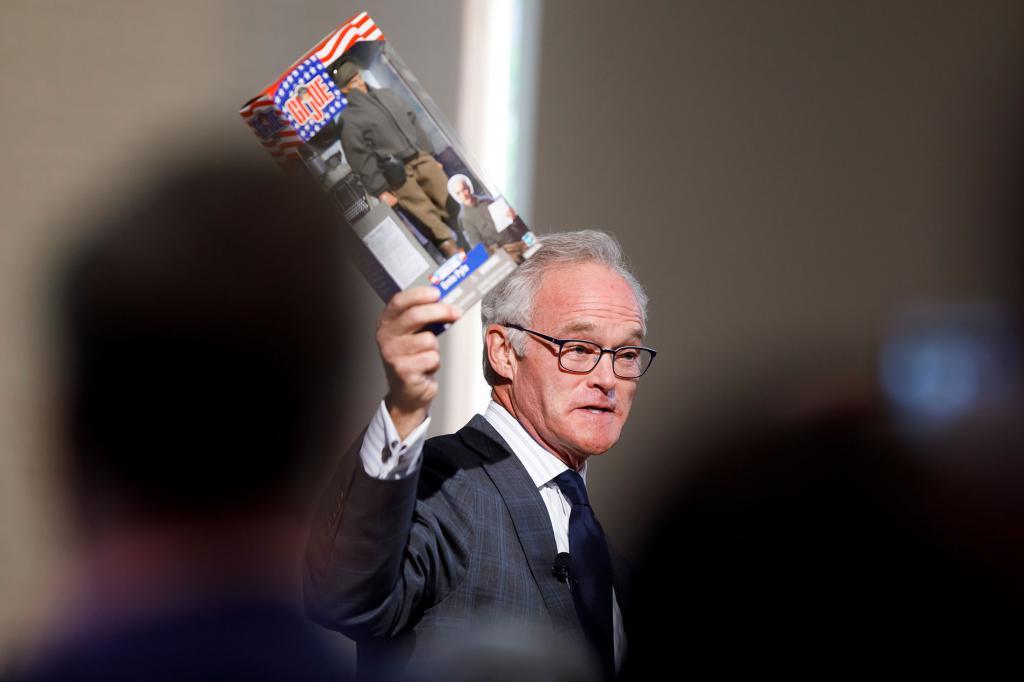 Scott Pelley holds up an Ernie Pyle G.I. Joe doll