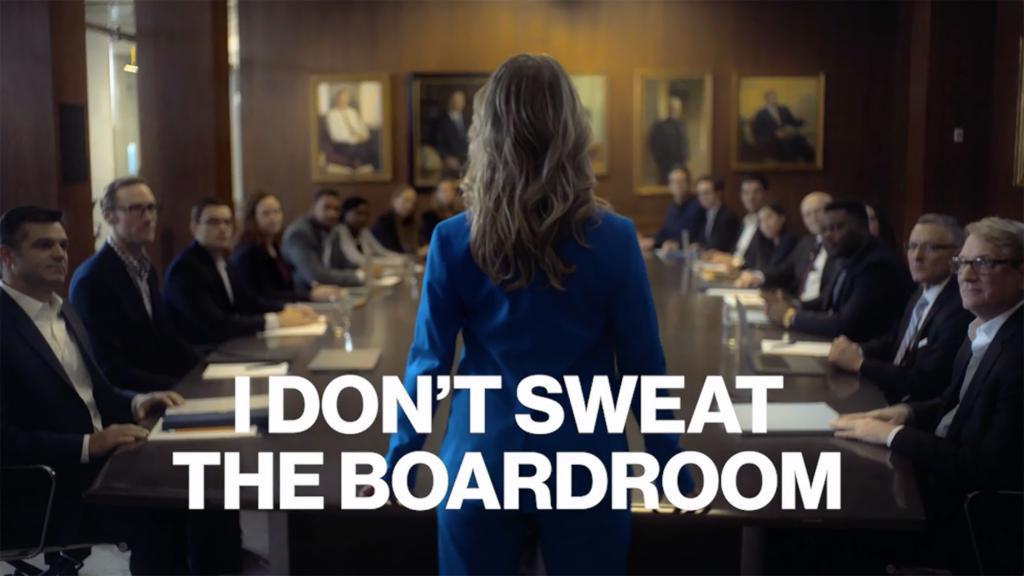 "A still from a Secret deodorant ad. A woman in a suit is standing at the front of a conference table. It says ""I DON'T SWEAT THE BOARDROOM."""