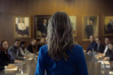 A still from a Secret deodorant ad. A woman in a suit is standing at the front of a conference table.