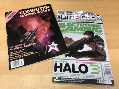 "Two magazines. One is Computer Gaming World. The cover says: ""LucasArts' X-Wing Fighter. Also in this issue: Global Effect, The Two Towers, Sea Rogues Strategy, Aces of the Pacific Tactics. 100 Games Rated!"" The second is Electronic Gaming Monthly. It says ""We played HALO. 14-page blowout! Exclusive new screens! Multiplayer Hands-On: New maps and modes. New Vehicles: Mongoose ATV, Brute Ghost. New Weapons: Brute Spiker, Spike grenades, Spartan laser, the new needler. Stuff for everyone from your best bud to the guy who slept with your gal."""