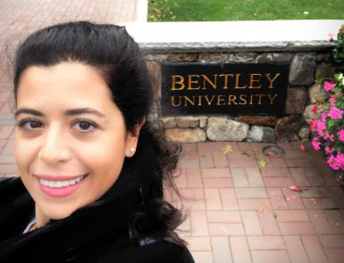 A selfie of Julide Etem in front of a Bentley University sign
