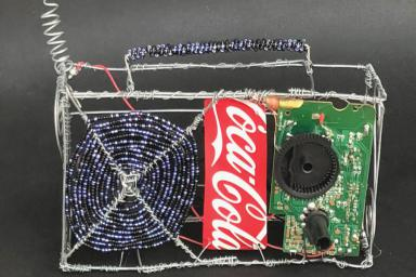 An artistic rendering of a radio made of recycled material: wire, a Coca-Cola can, beads.