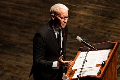 Anderson Cooper speaking at a podium into a microphone