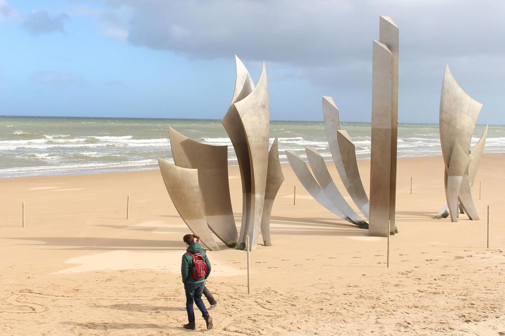 A student walks on a beach in Normandy.