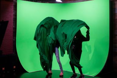 Two girls hide behind green sheets while standing in front of a green screen.