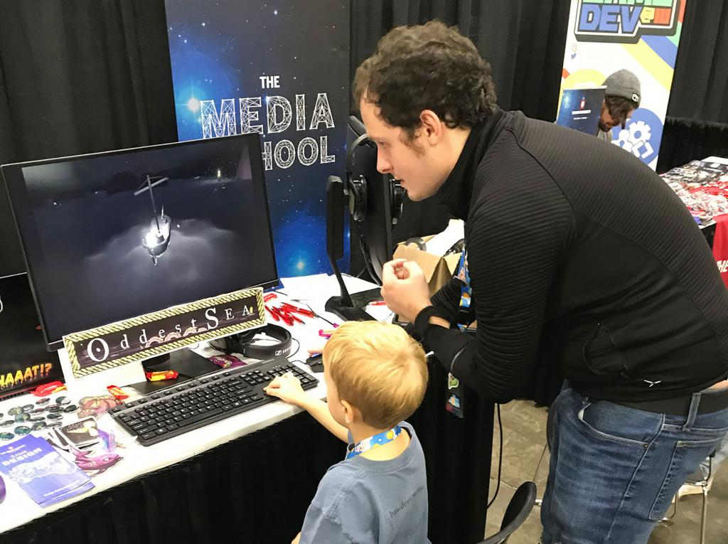 "Matt Olry shows a child how to play his video game, ""Oddest Sea"""