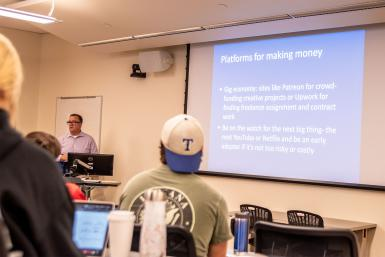 "Jay Kinciad teaches a class. His Powerpoint slide says: ""Platforms for making money. Gig economy: sites like Patreon for crowd-funding creative projects or Upwork for finding freelance assignment and contract work. Be on the watch for the next big thing -- the next YouTube or Netflix and be an early adopter if it's not too risky or costly."""