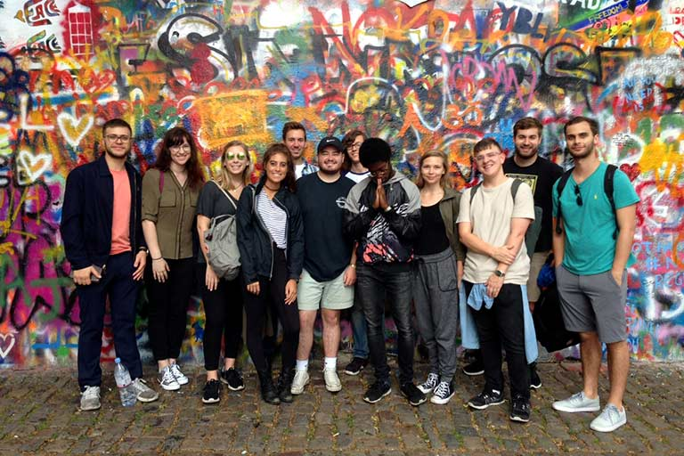 A group of students stands in front of the Lennon Wall in Prague.