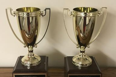 Two trophies. One says: