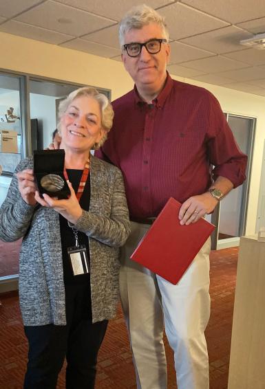 Dean James Shanahan presents undergraduate administrative services coordinator Marilyn Behrman with IU's Bicentennial medal.
