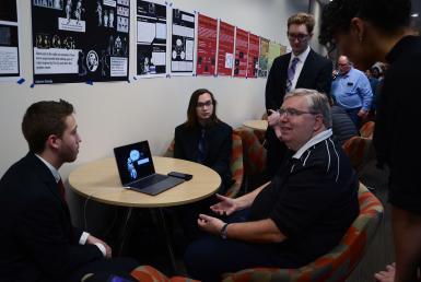 Paul Stephanouk, senior creative director at King, and CJ Ajawara, Blair Wheatley, Carson Hurwitz and Angel Aynes sit at a table and look at a computer.