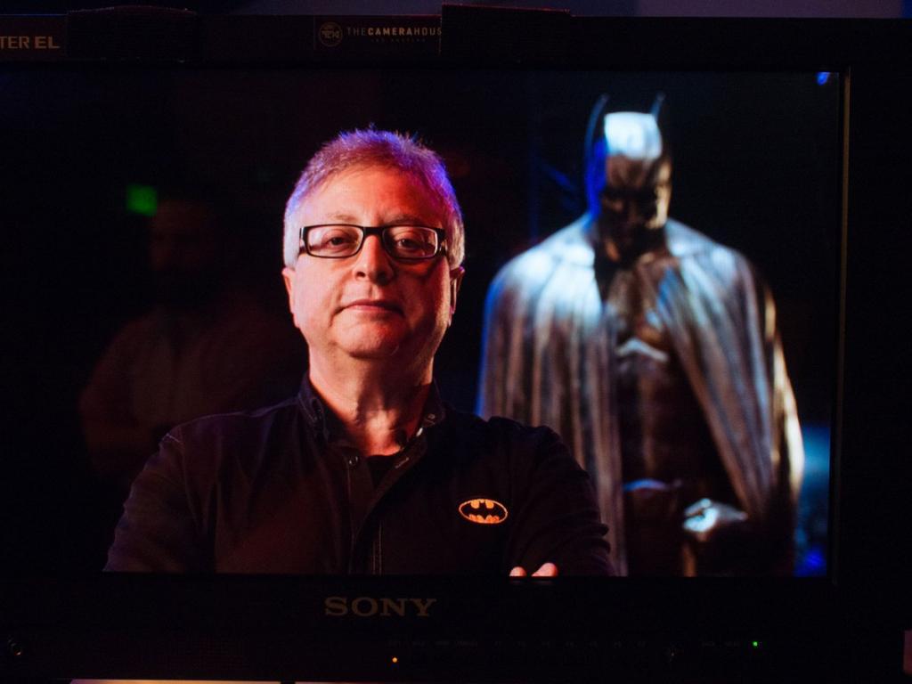 Michael Uslan standing in front of a Batman costume