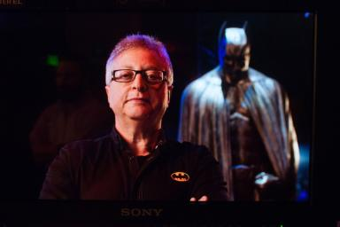 Michael Uslan standing in front of a Batman costume
