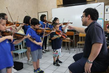 Rafael Kinoshita conducts an orchestra of child violinists