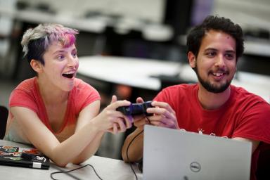 Two people sharing a game controller