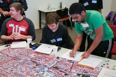Students gather around a map