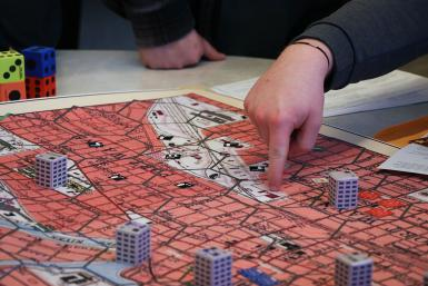Closeup of the game board, which looks like a city, and someone pointing at it