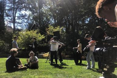 Students film a movie in a grassy area on campus.