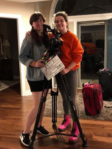 Katie Crump and Riley Dismore pose with a clapboard and a film camera on a tripod.