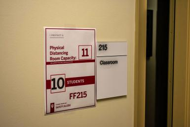 """A sign says """"Physica Distancing Room Capacity. 11. 10 students. FF215"""""""
