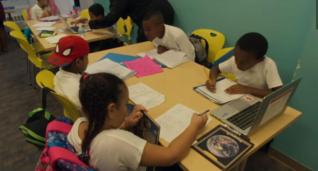 Children working on aschoolwork together at a table.