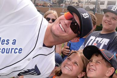 A baseball player takes a selfie with children