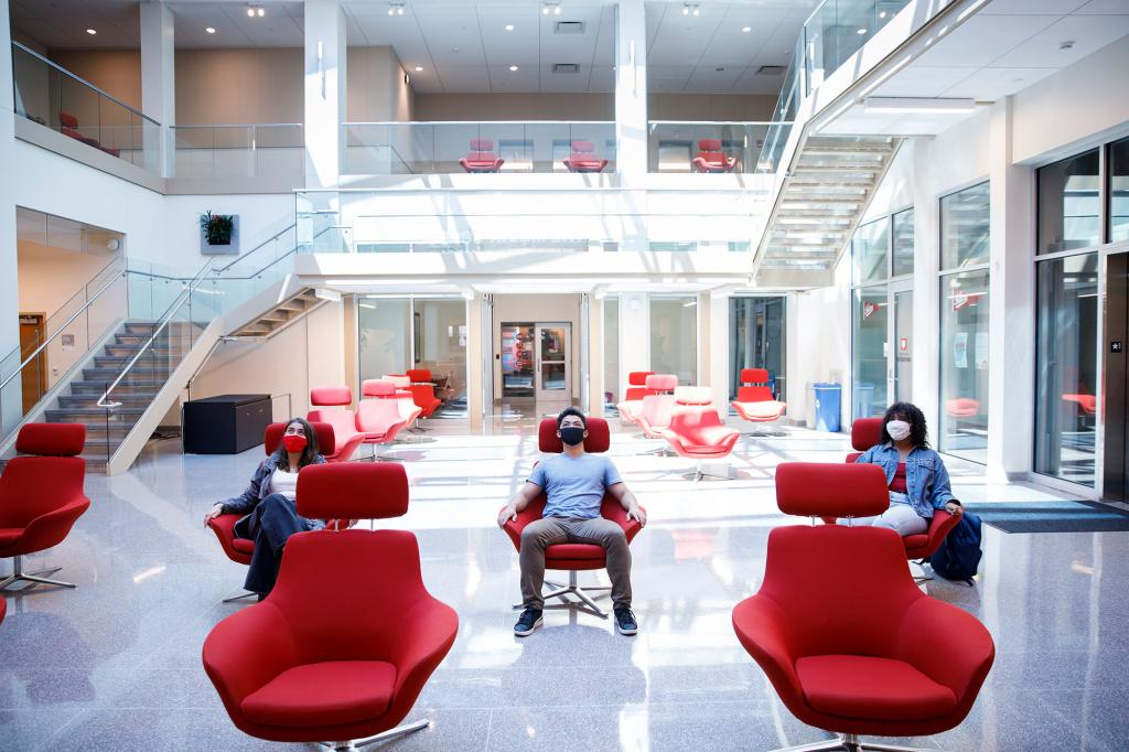 Three students sit in chairs in the Franklin Hall commons