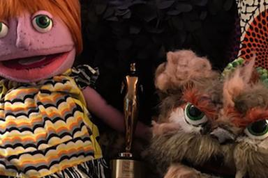 Two puppets hold three Telly awards.