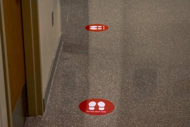 """A floor with two stickers that say """"Please Wait Here"""""""