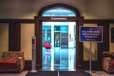 """A """"Welcome Back Media School Students"""" sign and a hand sanitizer dispenser sit outside the entrance to the Franklin Hall commons"""