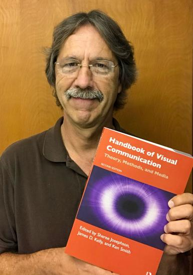 "Jim Kelly holding ""Handbook of Visual Communication"""