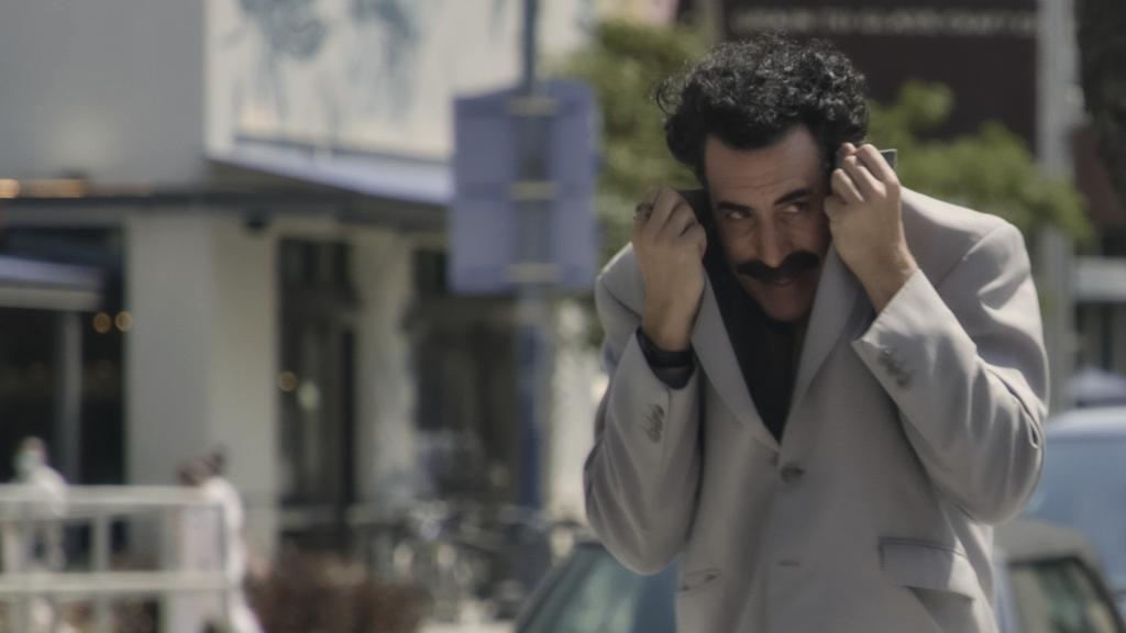 """Still image from """"Borat Subsequent Moviefilm."""" Borat is walking down the street covering his face with his coat."""