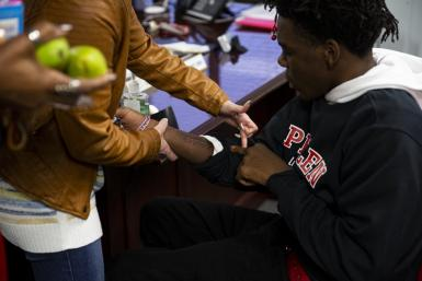 Nicole Fama, principal of James and Rosemary Phalen Leadership Academy, looks at one of Da'Quincy Pittman's scars on the forearm doctors sliced open to dig out a bullet.