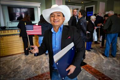 A man holds an American flag after his naturalization ceremony.