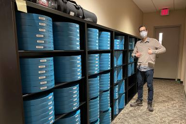 Dan Hassoun stands next to a bookcase of film canisters