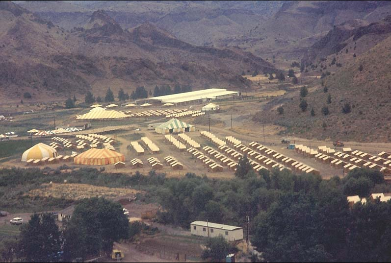 A community of tents surrounded by mountains