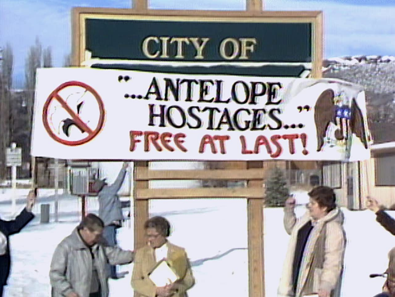 """A group of people in front of a sign. The words on the sign that are visible say """"City of."""" The rest of the sign is covered by a flag, that says """"... Antelop hostages ... free at last!"""""""