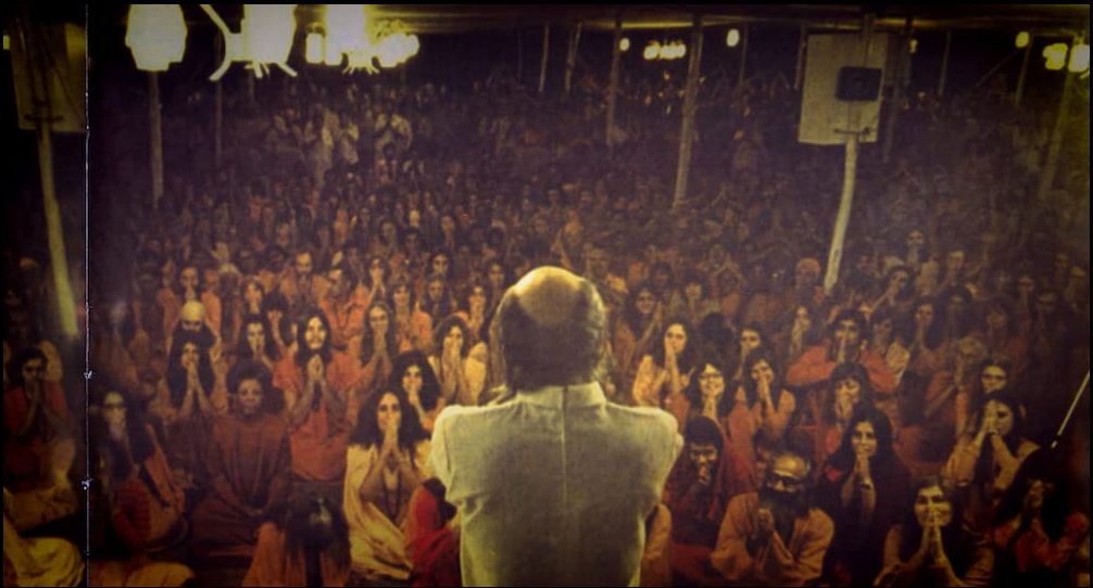 A man stands on a stage and looks out into a crowd of people