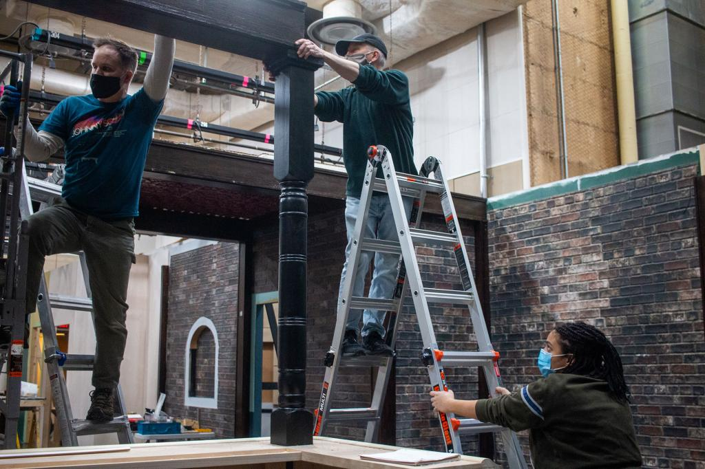 Media School students assist senior lecturers Craig Erpelding and Steve Krahnke in raising a large beam to support the ceiling in IU's new soundstage.